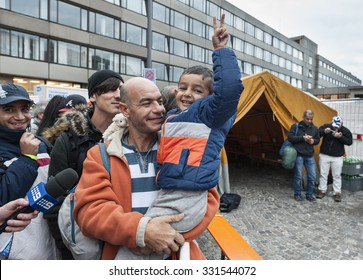 Munich, Germany -  September 7,  2015. Father and son from Syria are happy to arrive in Munich. Several hundreds of refugees arrive in only a few hours at Munich central station.