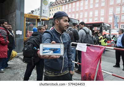 Munich, Germany - September 7, 2015: Refugee from Afghanistan demonstrates pictures of his getaway on a boat. Many refugees come to Europe via the mediterranian sea route.