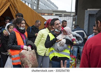 Munich, Germany - September 7th, 2015: A group of Syrian refugees with a small baby are very happy to get to Europe. Civil helpers supply the incoming refugees with warm clothes and blankets.