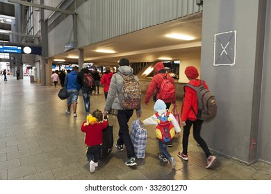 Munich, Germany -September 9, 2015: A young family from Syria hopping on the next train at the mainstation in Munich. The refugees are seeking asylum in Europe.