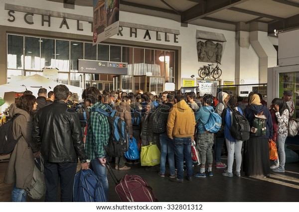 Munich, Germany - September 9, 2015: Refugees queuing up at the trainstation in Munich. The asylum seekers from Syria, Afghanistan and other insecure countries are happy to arrive in Germany.
