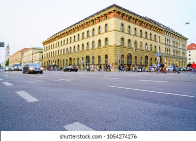 MUNICH GERMANY- SEPTEMBER 9; Imposing olive green building across intersection busy with people waiting, crossing and blurred vehicles passing along Ludwig Strasse  on September 9 2017, Munich Germanv