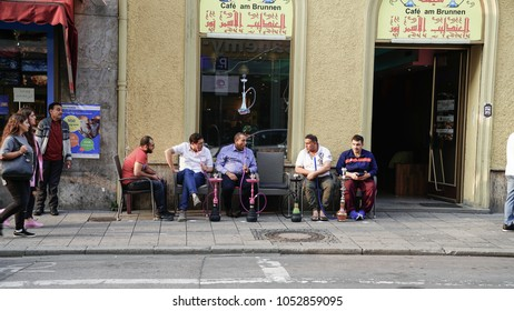 MUNICH GERMANY -SEPTEMBER 9; Middle Eastern men in Munich side street sitting outside shop on footpath talking  vaporizing flavored tobacco in hookah pipes  September 9 2017 Munich Germany