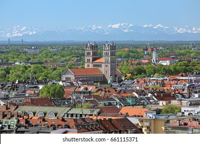 Munich, Germany. View of St. Maximilian Church from the tower of New Town Hall, and snow-covered peaks of Northern Limestone Alps in the background.