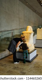 MUNICH - JUL 21, 2018 - Mother and child examine a statue in the Egyptian Museum, Munich, Germany