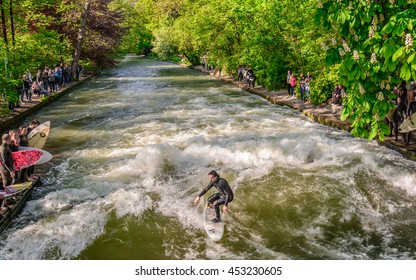 MUNICH (MUNCHEN), GERMANY - 05 MAY 2016: Several surfers practicing their skill on an artificial wave situated on a small channel (the Eisbach stream) in the Englischer Garten in central Munich