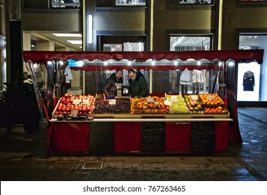 Munich - Nov 25, 2017: Two fruit vendors at their market stall are talking with each other.