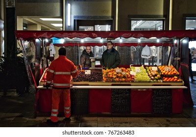 Munich - Nov 25, 2017: Two fruit vendors at their market stall talking to a garbage collecto