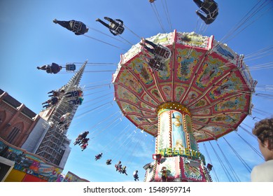 """Munich - Oct 27, 2019: The swing ride is the main attraction at the """"Auer Dult"""" county fair in Munich, right in front of the Mariahilf church."""