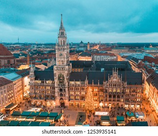 Munich Rathaus and main square with Christmas tree and decorations at night. Bavarian capital city during Christmas time with markets and lights, aerial view, toned image