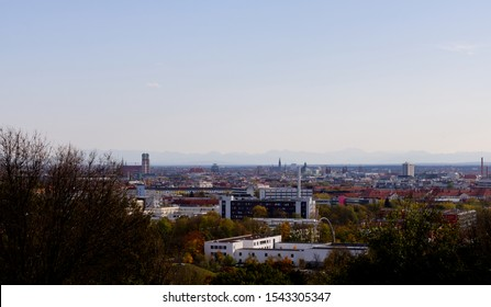 Munich skyline with the Frauenkirche church photographed from the Olympia hill in Munich Olympiapark on a clear day with the Alps on the background