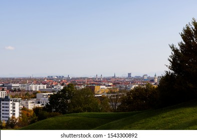 Munich skyline photographed from the Olympia hill in Munich Olympiapark on a clear day with the Alps on the background