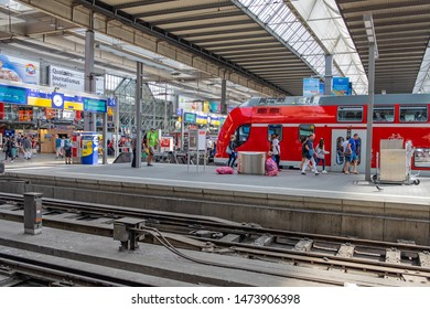 Munich,Bavaria, Germany- 08 August 2019: A Central Station of Munich with many people and tourists moving around in the Hall Plattform, the regional intercity red trains