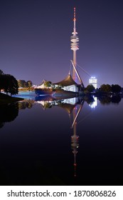 Munich-Bavaria-Germany - 09-09-2020: Skyline in Munich. Reflecting lake in the Olympiapark in Munich at night. Skyline reflections in Munich.