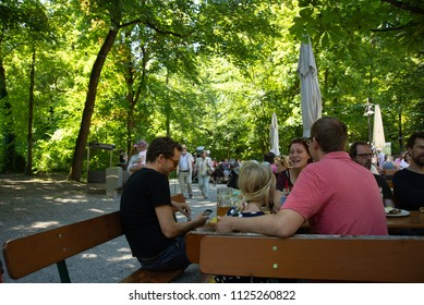 Munich,Germany-01 July,2018: People have lunch under the shade of trees in a biergarten