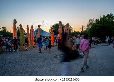Munich,Germany-July 13,2018: A family looks at lit wooden statues at the Toll Wood Festival shortly after sunset