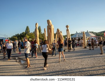 Munich,Germany-July 13,2018:People walk past wood sculptures in the summer Tollwood Festival