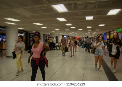 Munich,Germany-July 13,2018:People walk in the undereground concourse under Munich Central Station past security personnel and paramedics attending to a sick person.