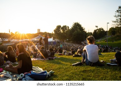 Munich,Germany-July 13,2018:People watch the sunset on a hill overlooking the Tollwood Festival in Munich's Olympic Park