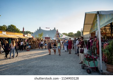 Munich,Germany-July 13,2018:Visitors walk past clothing stalls in the summer Tollwood Festival