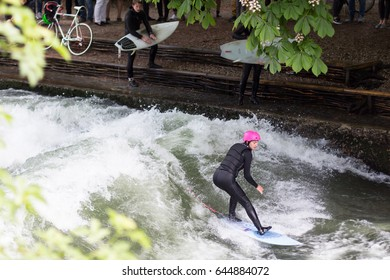 MUNICH,GERMANY-MAY 21:  Surfer girl on the Eisbach in the English Garden in Munich on May  21, 2017 in Munich, Germany. This river flows through the Englischer Garden and is a popular river surf spot.