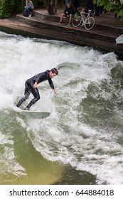 MUNICH,GERMANY-MAY 21:  Surfer man on the Eisbach in the English Garden in Munich on May  21, 2017 in Munich, Germany. This river flows through the Englischer Garden and is a popular river surf spot.