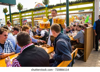 Munich,Germany-September 24,2017: A waiter arrives at table  carrying fresh Beer mugs in a Biergarten at the Oktoberfest