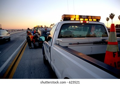 Municipal roadside assistance helping to tow away a broken car off the freeway at sunset