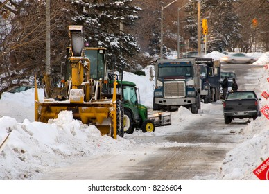 Municipal snow removal crew; giant snow thrower, trucks lined up to cart away the snow, and small plow.