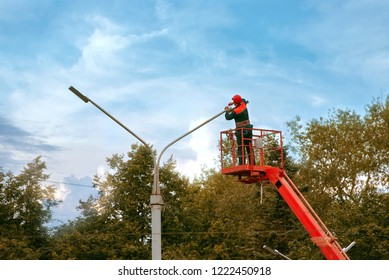 Municipal worker man with helmet and safety protective equipment installs new diode lights. Worker in lift bucket repair street light pole. Modernization of street lamps. Technician on aerial device