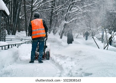 Municipal worker removing snow from the moscow street using snow blower after big snowfall