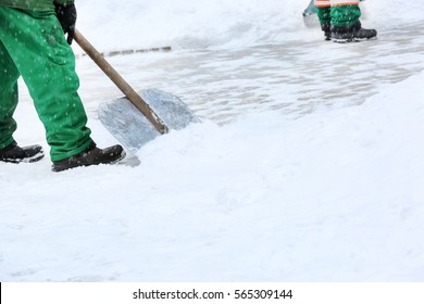 Municipal worker removing snow with shovel