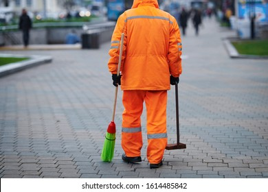 Municipal worker sweep pavement,  janitor with broomstick and dustpan for garbage in hands. Municipal worker in orange uniform collecting garbage from road and walkway. City cleaner