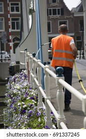 municipality worker is flowering the hanging flower pots on the side of the bridge with a garden hose