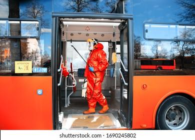 Trabajador municipal que realiza la desinfección con un limpiador líquido en el transporte público (autobús) durante el brote de Covid-19 - Vilnius, Lituania, Europa