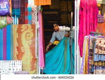 Munnar, Kerala, India - Circa November 2012 - Portrait of an unidentified apparel store owner folding the fabrics in Munnar, Kerala, India