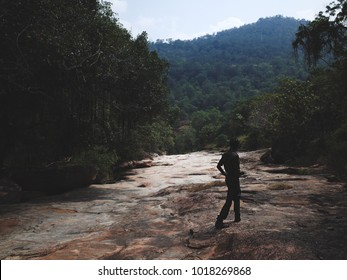 Munnar, Kerala, India- January 2018: A forest guide walks across a rocky landscape in Chinnar wildlife sanctuary