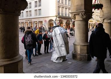 MUNSTER, NORTH RHINE-WESTPHALIA / GERMANY - DECEMBER 16, 2018: Unusual street artist pantomime interested children