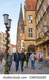MUNSTER, NORTH RHINE-WESTPHALIA / GERMANY - DECEMBER 16, 2018: People walk around the festively decorated center of the city before Christmas.