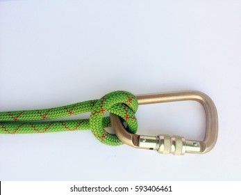 a munter hitch on a green rope tied around a bronze carabiner
