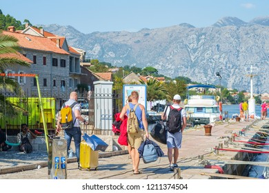 Muo, Montenegro – October 13, 2018: Tourists with suitcases, backpack and bags walk along the yachts and motorboats moored at the pier to their motorboat. In the background you can see mountains
