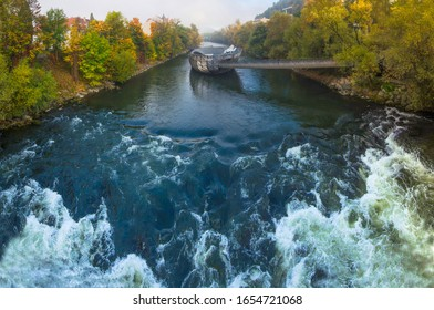 Mur river in autumn, with Murinsel bridge and old buildings in the city center of Graz, Styria region, Austria.