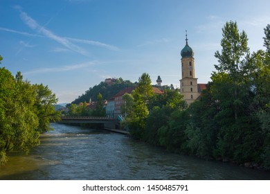 Mur river, the Franciscan Church tower and the famous clock tower (Grazer Uhrturm) in the background, in the centre of the city of Graz, Styria region, Austria