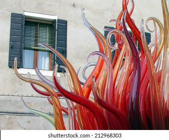 Murano glass (closeup detail of street monument of Murano island) on a background of house - looking like a fire