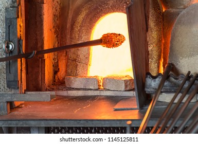 Murano glass-blowing factory. Glass blower forming beautiful piece of glass: put iron rod with attached glass object in furnace to make the glass malleable. Venice, Italy