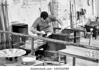 Murano island, Italy - April 23, 2017: Glassblowing artisan at work in a crystal glass workshop in Murano island, Venice.