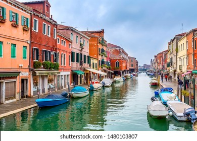 Murano island, Venice, Italy - November 11, 2014: Canal with boats, colorful houses and people at the street
