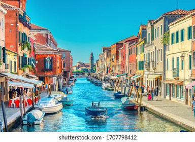 Murano islands, bridge across water canal, boats and motor boats, colorful traditional buildings, Venetian Lagoon, Veneto Region, Northern Italy. San Michele in Isola Catholic church background