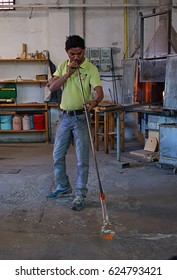 Murano, Italy - 09 October, 2013: an apprentice of a master in a famous Murano glass factory blowing a glass statue during a show