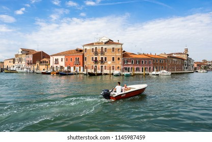 MURANO, ITALY - JUNE 24, 2018: A motorboat in Murano, typical buildings on the background